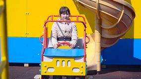 Девушка управляет автомобилем на карусели сток-видео