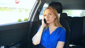 Девушка управляет в автомобиле рядом с водителем и говорит на телефоне сток-видео