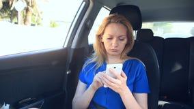 Девушка управляет в автомобиле рядом с водителем и говорит на телефоне видеоматериал