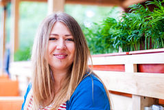 Девушка усмехаясь в кафе Девушка помадки толстенькая Стоковые Изображения