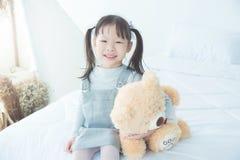 Девушка усмехаясь пока обнимающ заполненного медведя на кровати Стоковые Изображения