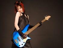 Девушка утеса с голубой басовой гитарой стоковые фотографии rf