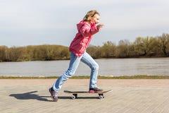 Девушка уча ехать скейтборд стоковые изображения rf