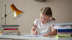 Девушка уча уроки, милую девушку делая ее домашнюю работу, школьницу studing дома на таблице сток-видео