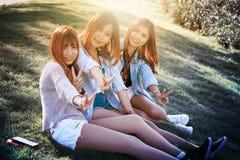 Девушка улыбки 3 Азия сидит на зеленой траве Стоковое Изображение