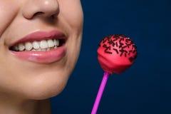 Девушка улыбки с красными cakepops Стоковое Фото