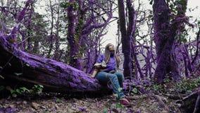 Девушка фиолетового леса сказки счастливая в непринужденном стиле сидит на покрытом мх пурпурном дереве и смотрит вверх в a акции видеоматериалы