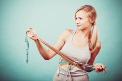 Девушка фитнеса измеряя ее тело с лентами Стоковые Изображения