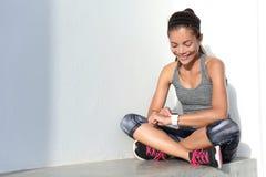 Девушка фитнеса используя smartwatch отслежывателя деятельности как монитор тарифа сердца для разминки Стоковые Изображения RF