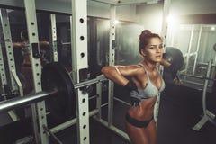 Девушка фитнеса отдыхая после поднимать штангу Стоковое Изображение