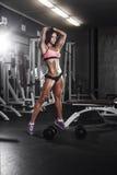 Девушка фитнеса при гантели представляя в спортзале Стоковое фото RF