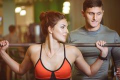 Девушка фитнеса при штанга работая с тренером Стоковое Изображение