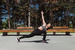 Девушка фитнеса протягивая в парке города стоковые изображения rf