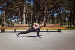 Девушка фитнеса протягивая в парке стоковые изображения