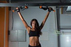 Девушка фитнеса работает на турнике в спортзале спорта, заднем взгляде активный уклад жизни Стоковое фото RF