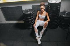 Девушка фитнеса сидя между тяжелыми весами для штанги Фотомодель спорта Правильное питание Разминка фитнеса спорта стоковые фотографии rf