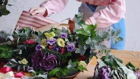 Девушка флориста делает большой современный букет из различных цветков стоковое фото rf