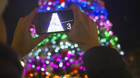 Девушка фотографирует на предпосылке украшений рождества в парке сток-видео