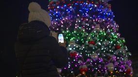 Девушка фотографирует на предпосылке украшений рождества в парке акции видеоматериалы