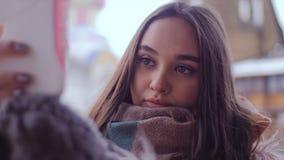 Девушка фотографирует на телефоне акции видеоматериалы