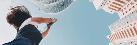 Девушка фотографирует новый жилой комплекс Белые новые современные небоскребы стоковые фото