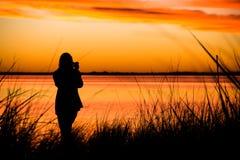 Девушка фотографируя заход солнца Стоковое фото RF