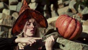 Девушка хеллоуина Игра девушки с тыквами и обслуживанием Милая ведьма с тыквой Удивленная женщина с тыквой хеллоуина сток-видео