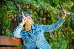 Девушка хипстера делает selfie в парке Время Selfie Ослабьте на стенде мода весны хипстера видео конференц-связь hi я здесь стоковое изображение