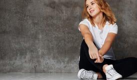 Девушка хипстера нося пустую белую футболку, джинсы против стены, стоковое изображение