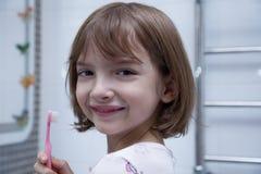 Девушка чистя ее зубы щеткой в ванной комнате стоковое изображение
