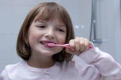 Девушка чистя ее зубы щеткой в ванной комнате стоковое фото