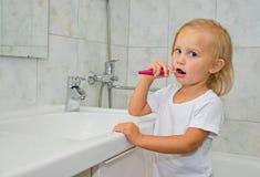Девушка чистя ее зубы щеткой в ванной комнате Стоковая Фотография