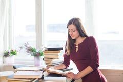 Девушка читает книги на таблице окном Стоковое Фото