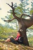 Девушка читает книгу в лесе осени стоковое изображение rf