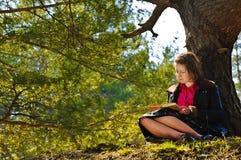 Девушка читает книгу в лесе осени стоковая фотография rf