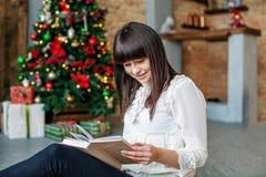 Девушка читает книгу дома Счастливого рождества концепции, комфорт, Стоковые Изображения
