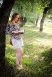 Девушка читает книгу около дерева Стоковые Изображения RF