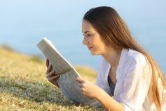 Девушка читая газету на траве Стоковые Изображения RF