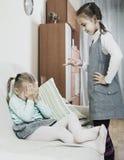 Девушка читая лекцию маленькая сестра в отечественном интерьере Стоковое Изображение