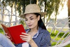 Девушка читая книгу в саде стоковое изображение rf
