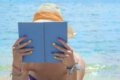 Девушка читая книгу на пляже Стоковое Изображение RF
