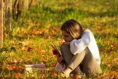 Девушка читая книгу сидя в природе стоковое изображение rf