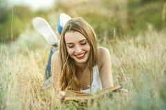 Девушка читая книгу снаружи Стоковая Фотография