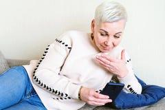 Девушка читая SMS в смартфоне Эмоция радостного сюрприза Стрижка женщин короткая Модный стильный профиль с стоковые изображения