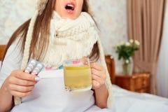 Девушка чихает с кружкой чая и медицин в ее руке стоковое фото rf