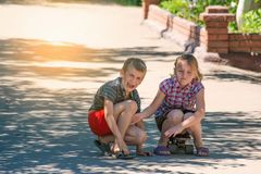 Девушка чувствует к сожалению для мальчика, ее брата, который был ранен пока едущ скейтборд на дороге в улице стоковая фотография rf