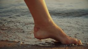 Девушка шагая на влажный песок бечевника Ноги молодой женщины идя вдоль океана приставают к берегу во время захода солнца Молодая видеоматериал