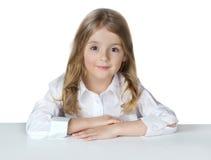 Девушка школы ребенка изолированная на белизне сидит на таблице Стоковое фото RF