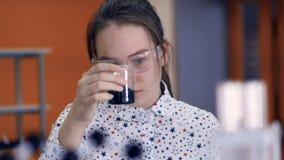 Девушка школы химика 10-11 лет в стеклах смешивая химикаты в пробирке видеоматериал