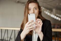 Девушка шпионила на парне но получила уловленной Портрет красивой европейской женщины сидя в кафе, пробуя принять фото Стоковая Фотография